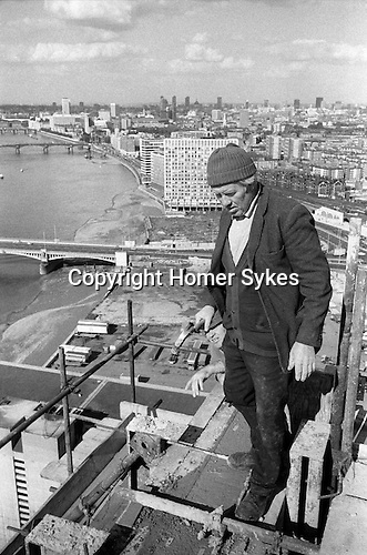 Irish labourers construction workers holdinmg hammer at the top of and working on a Nine Elms tower block. London skyline and River Thames. England 1974