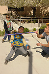 Isaac Ledezma, 6, makes it under the bar in a limbo contest during the 7th Annual Easter Fiesta at Western Nevada College Saturday, March 26, 2016. Adrian Barrera, 18, holds the bar as Gage Kingsland, 6, looks on. The event, hosted by the Association of Latin American Students, had 3 separate egg hunts, face painting, limbo, musical chairs, ring toss, sack races, bowling,  food, music and a piñata.  <br />