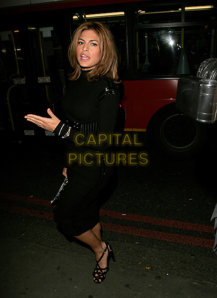 EVA MENDES.Attends Mulberry For Giles Bags - Launch Party at Harvey Nichols, Knightsbridge, London, England, .January 30th 2007..full length black top polo neck waist belt patent pencil skirt strappy shoes sandals hand blowing kiss gesture.CAP/AH.©Adam Houghton/Capital Pictures.