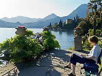 Italien, Lombardei, Comer See, Varenna: im Park der Villa Monastero, Frau auf einer Bank, liest | Italy, Lombardia, Lake Como, Varenna: at Park of Villa Monastero, woman on bech reading