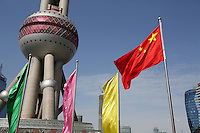 A Chinese national flag flying in front of the Oriental Pearl Tower.<br />