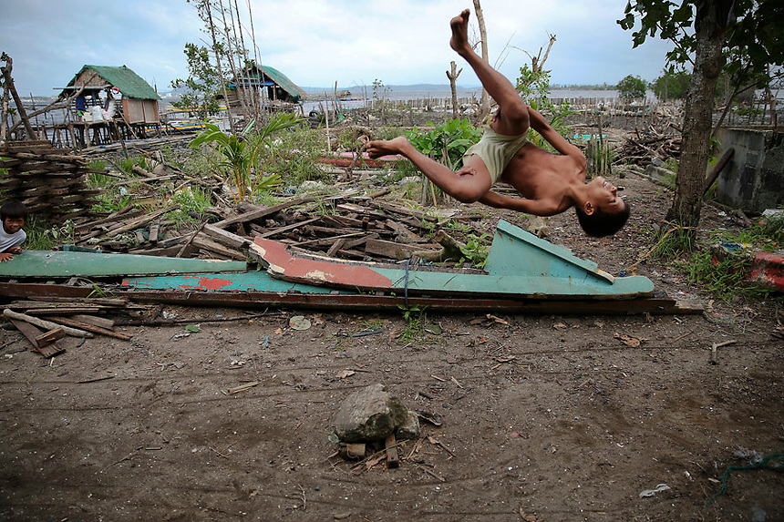 A boy makes a flip in the coastal part of Tacloban that was destroyed by Typhoon Haiyan January 16, 2015. On his first visit to Asia's largest Catholic nation, Pope Francis will visit the central province of Leyte, which is still struggling to recover from Typhoon Haiyan that killed 6,300 people in 2013. About two million people are expected to attend an open-air mass on Saturday at Tacloban City airport, almost completely destroyed by Haiyan. REUTERS/Damir Sagolj (PHILIPPINES)