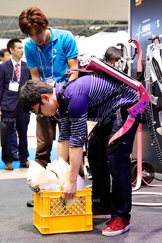 "A visitor carries a heavy box using the ""Wearable Robot Muscle Suit"" at the Japan Robot Week 2014 on October 16, 2014 in Tokyo, Japan. Companies at the ""Japan Robot Week 2014"" exhibited their latest high-tech nursing and life supporting robots. The 2014 edition of the show ran from October 15 to 19 at Tokyo Big Sight. (Photo by Rodrigo Reyes Marin/AFLO)"