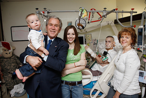 Washington, DC - December 22, 2008 -- United States President George W. Bush holds 15-month-old James Jensen, son of  Purple Heart recipient United States Army Corporal Isaac Jensen of Layton, Utah, background-right, while posing for a photo Monday, December 22, 2008 with Corporal Jensen, his wife, Bethany and his mother, Eva Francis, right, during President Bush's visit to Walter Reed Army Medical Center in Washington, D.C. Jensen is recovering from injuries sustained while serving in support of Operation Iraqi Freedom. .Credit: Eric Draper - White House via CNP