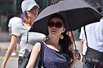 July 8, 2011 - Tokyo, Japan - A woman is seen holding a fashionable parasol in downtown Tokyo. Japanese people, especially middle-aged women, use parasols during the hot Summer months to avoid any form of skin cancer. Today, parasols are also becoming popular among young adult women due to various designs and colors available on the market. (Photo by Yumeto Yamazaki/AFLO)