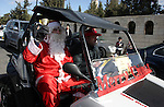 A man dressed as Father Christmas drives past the Israeli built separation barrier as Christians arrive to celebrate Christmas mass in the West Bank city of Bethlehem, on December 24, 2011. Photo by Issam Rimawi