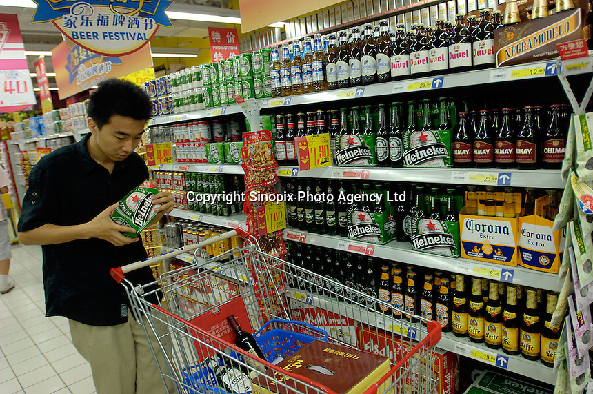 A man looks at Heineken beer at Heineken , Corona, Budweiser and other brand beers shelves in a Carrefour supermarket in Beijing, China. Major international chains like Carrefour and Walmart Stores have expanded aggressively in China. Local Chinese retailers have loudly protested this and lobbied heavily for protection from the new competition in price and service that these major retailers have set off..23 Jul 2006