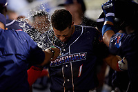 Jacksonville Jumbo Shrimp shortstop Joe Dunand (1) is splashed with water by his teammates in the dugout after hitting a home run in the top of the sixth inning during a game against the Pensacola Blue Wahoos on August 15, 2018 at Blue Wahoos Stadium in Pensacola, Florida.  Jacksonville defeated Pensacola 9-2.  (Mike Janes/Four Seam Images)