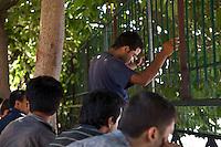 Grecia, Patrasso 2011: rifugiati afghani in un improvvisato campo in una stazione ferroviaria abbandonata. Un gruppo di uomini seduti all'ombra di alcuni alberi. Un uomo ha le mani appoggiate sulle sbarre di un cancello. Grece  patras refugies afghans dans une gare abandonee