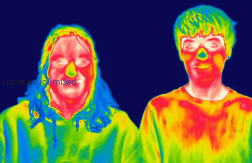 Thermogram of a male teenager and an adult woman. The temperature scale runs from white (warmest) through red, yellow, green and cyan, blue and black (coldest).