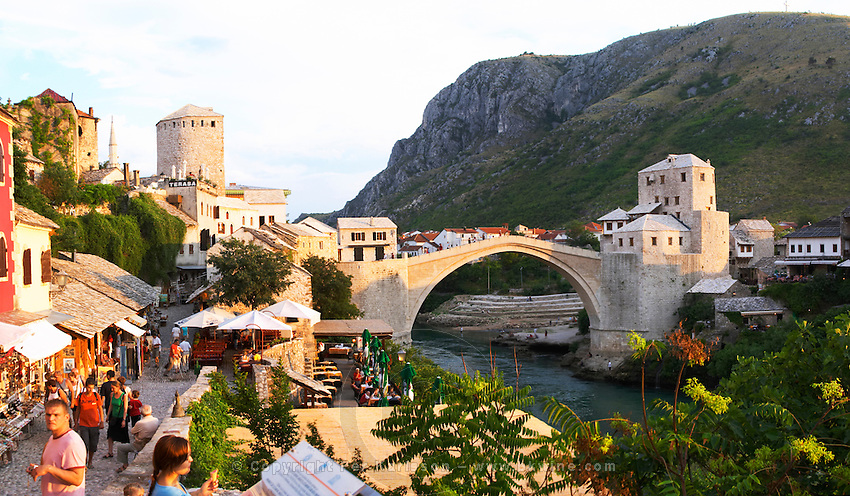 Panorama of the busy old market bazaar street Kujundziluk with lots of tourist craft and art shops and street merchants. Sunset late afternoon light. View along the river of the old reconstructed bridge. Restaurants cafes along the river bed. Historic town of Mostar. Federation Bosne i Hercegovine. Bosnia Herzegovina, Europe.