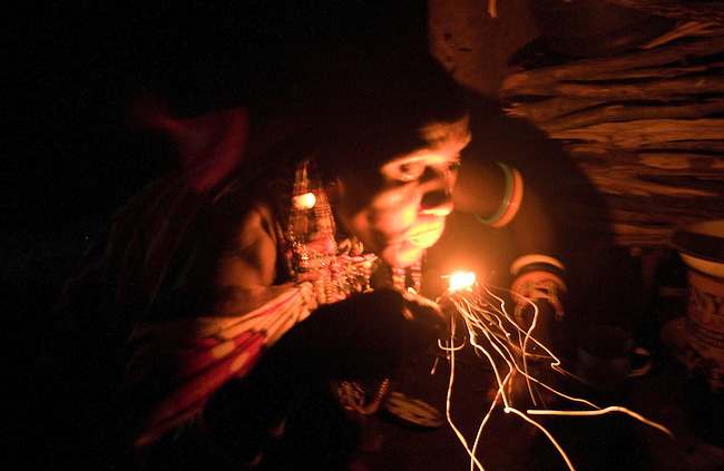 Masai woman blowing on fire inside her manyatta, Kenya.