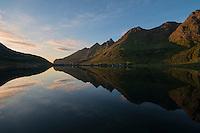 Mountains reflect in calm Fjord on summer evening, Skjelfjord, Flakstadøy, Lofoten Islands, Norway