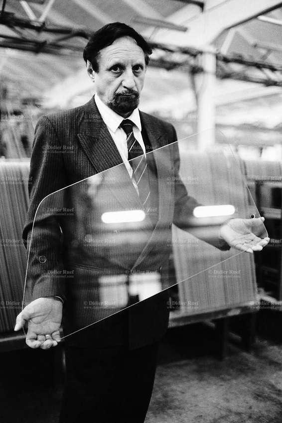 Italy. Tuscany Region. Pisa. St Gobain glass plant. Glass recycling. A manager holds in his hands a new FIAT Tipo side window which was checked for any anomalities in the recycling glass structure. © 1993 Didier Ruef .