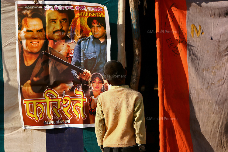 06.11.2008Pushkar(Rajasthan)<br /> <br /> Child looking a poster of indian movie in the entrance of a nomadic cinema during the pushkar cattle fair.<br /> <br /> Enfant regardant l affiche d un film indien a l' entrée d un cinema nomade pendant la foire au betail de pushkar.