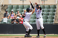 Seby Zavala (21) of the Kannapolis Intimidators celebrates at home plate with teammate Brandon Dulin (31) after hitting a go-ahead 3-run home run against the West Virginia Power at Kannapolis Intimidators Stadium on June 18, 2017 in Kannapolis, North Carolina.  The Intimidators defeated the Power 5-3 to win the South Atlantic League Northern Division first half title.  It is the first trip to the playoffs for the Intimidators since 2009.  (Brian Westerholt/Four Seam Images)