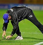 Terry Butcher takes on the job of the Motherwell groundsman for a laugh much to the delight of the home fans and replaces a divot during the second half