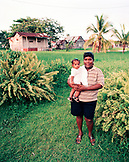 PANAMA, Bocas del Toro, a woman stands in her yard holding her daughter, Central America