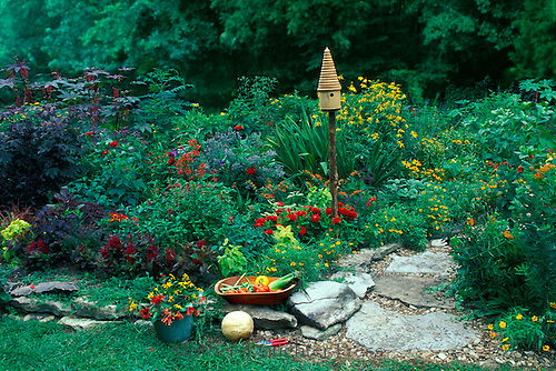 Conical birdhouse and stone walkway meet at the edge of the garden where the vegetable harvest has been collected