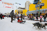Saturday March 6 , 2010  Honorary musher Oren Seybert of Pennair rides in the sled basket of 2010 Jr. Iditarod champion Merrissa Osmar during the ceremonial start of the 2010 Iditarod in Anchorage , Alaska