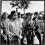 "Elementary schoolchildren in Hulan county read the Little Red Book on their way to a study session of Mao's writings. The boy's sash reads, ""It is right to rebel."" Heilongjiang province, 23 July 1967"