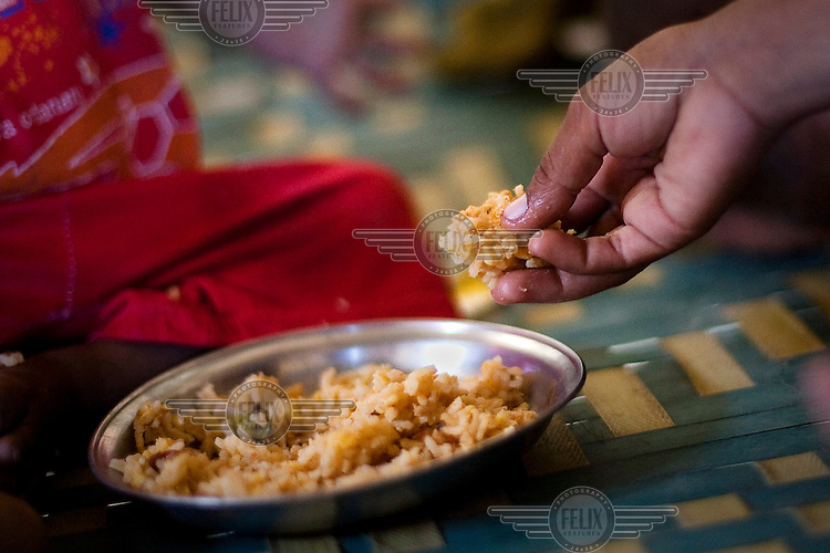 A child eats a dish of rice at their family home. Poor diet and food hygiene is one of the contributing factors that annually produce very high levels of malnutrition amongst children.