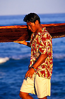 """Young man getting ready to surf at """"""""Pines"""""""" on the Big Islands"""