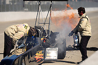 Feb. 27, 2011; Pomona, CA, USA; NHRA safety safari personnel tend to top fuel dragster driver Troy Buff after exploding an engine during the Winternationals at Auto Club Raceway at Pomona. Mandatory Credit: Mark J. Rebilas-
