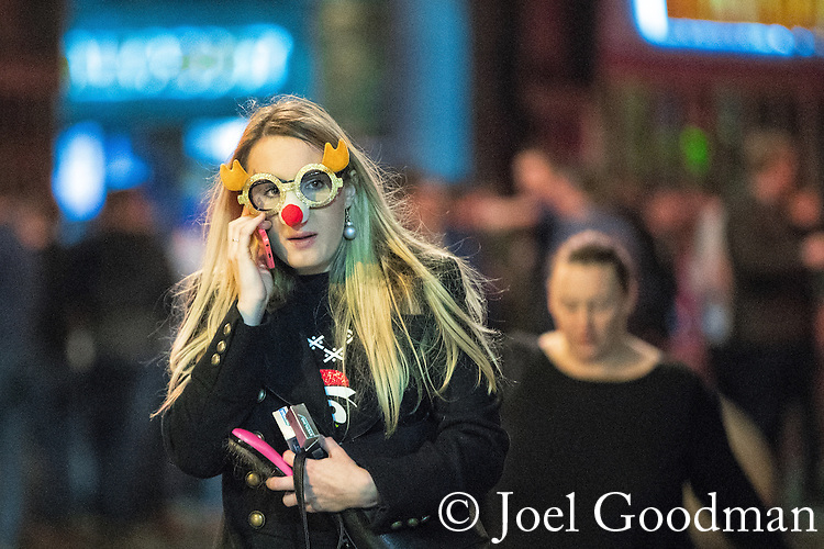 "© Joel Goodman - 07973 332324 . 17/12/2016 . Manchester , UK . A woman wearing novelty reindeer glasses . Revellers out in Manchester City Centre overnight during "" Mad Friday "" , named for being one of the busiest nights of the year for the emergency services in the UK . Photo credit : Joel Goodman"