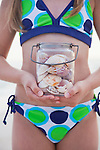 USA, Florida, St. Pete Beach, Girl (8-9) holding jar of seashells on beach, mid section