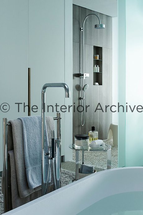 A contemporary bathroom in cool tones of blue and grey and polished steel fittings.