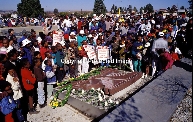 digasow00006 .South African Places. Gauteng. Soweto. Unidentified school children paying respect to Hector Peterson outside the newly opened Hector Peterson museum on June 16, 2002 in Soweto, South Africa. Hector Peterson was killed during the student uprising in Soweto in 1976, where black students demonstrated against the Afrikaans language imposed by them by the Apartheid government. The new museum opened on Youth Day June 16, 2002..©Per-Anders Pettersson/iAfrika Photos