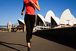 A woman runs along Sydney Harbour in front of the Opera House.  Sydney, New South Wales, AUSTRALIA.