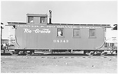 Side view of long caboose #04343, at Alamosa, flying herald, round roof.<br /> D&amp;RGW  Alamosa, CO  Taken by Richardson, Robert W. - 10/1950