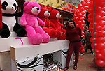 A Palestinian woman poses for a photo with red teddy bears outside a shop on Valentine's day in Gaza city on February 14, 2017. Valentine's Day is increasingly popular in the region as people have taken up the custom of giving flowers, cards, chocolates and gifts to sweethearts to celebrate the occasion. Photo by Ashraf Amra