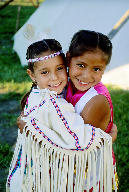 Native American family of two sisters, elementary school age, hugging while dressed in their traditional regalia and jingle dress during a Pow wow in Fort Hall, Idaho