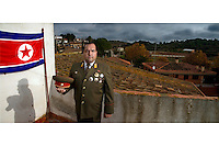 A portrait of Alejandro Cao de Benos, photographed in the village of Salomo in northeast Spain wearing his uniform and standing next to the North Korean flag. As a Korean-Spanish communist, Alejandro is the president of the Korean Friendship Association (KFA) and has been an advocate of the Democratic People's Republic of Korea (North Korea) since 1990. His Korean name is Zo Sun-il (Korea is One) and he works as an honorary Special Delegate of the DPRK's Committee for Cultural Relations with Foreign Countries - a North Korean government spokesman in Europe.