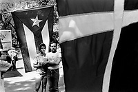 USA. New York. Central Park. A couple stands in between two puerto rican flags on The National Puerto Rican Day. The Puerto Rican Day Parade (also known as the National Puerto Rican Day Parade) takes place annually along Fifth Avenue in New York City, on the second Sunday in June, in honor of the nearly 4 million inhabitants of Puerto Rico and all people of Puerto Rican birth or heritage residing in the mainland U.S. © 1986 Didier Ruef