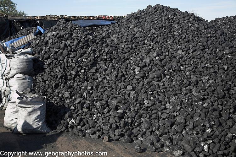 Piles of coal in a coal merchants yard, Rackhams, Wickham Market, Suffolk, England