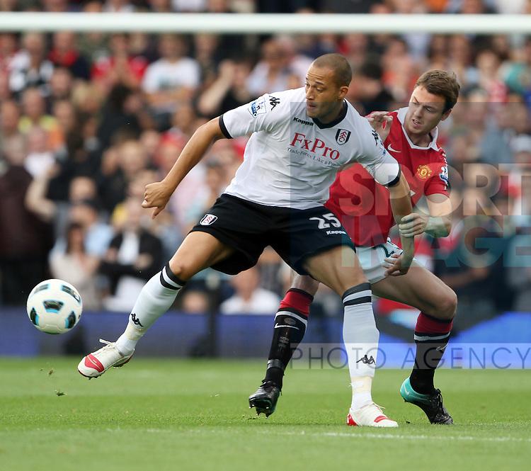 Fulham's Bobby Zamora tussles with Manchester United's Jonny Evans