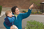 """22 month old toddler boy outside with mother signing """"bird"""" as his mother points at bird (bird not visible)"""