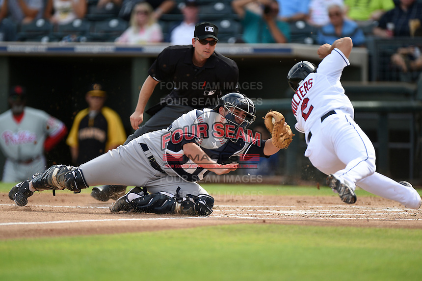 Scottsdale Scorpions catcher Kyle Higashioka (58) tags out Tony Wolters (2) sliding into home as umpire Greg Stanzak looks on to make the call during an Arizona Fall League game against the Peoria Javelinas on October 18, 2014 at Surprise Stadium in Surprise, Arizona.  Peoria defeated Scottsdale 4-3.  (Mike Janes/Four Seam Images)