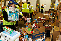 """Volunteer Nan Elliot places tissue boxes in the pile destined for the Grayling checkpoint durnig  the """"people food packing day"""" to be sent out to the 22 checkpoints on the 2019 Iditarod Trail at the Airland Transport warehouse in Anchorage on Friday February 15, 2019.<br /> <br /> Photo by Jeff Schultz/SchultzPhoto.com  (C) 2019  ALL RIGHTS RESERVED"""