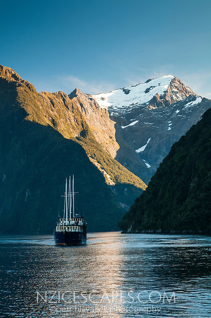 Boat  in Harrison Cove in Milford Sound. Mt. Pembroke in background, Fiordland NP, Southland, New Zealand