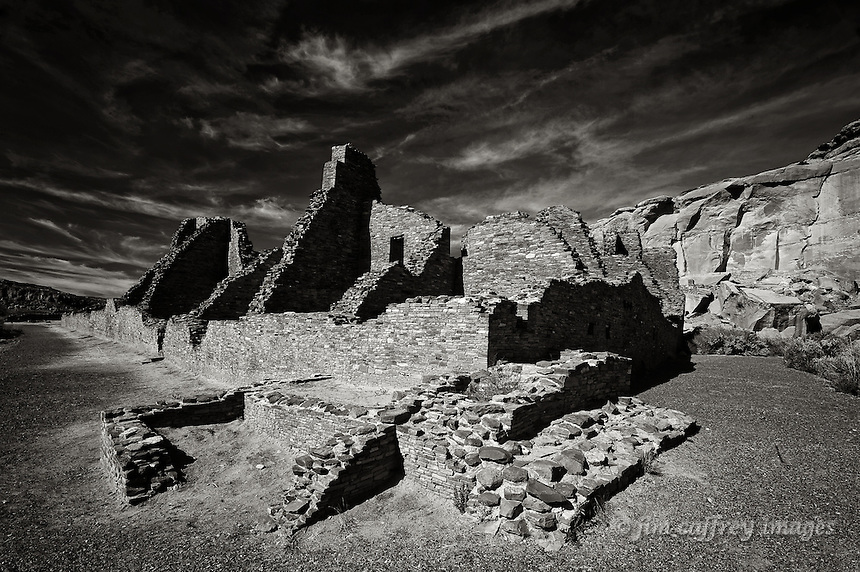 A black and white image of the south and eastern walls of Pueblo Bonito in Chaco Canyon National Historical Park in the San Juan Basin of northwestern New Mexico.