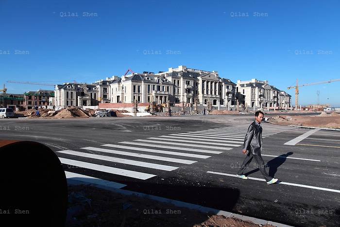 "A man walks past at the site of a new luxury housing development being built in the middle of the dessert near the Kangbashi New District of Ordos City, Inner Mongolia, China on 16 August, 2011. With an investment of over 161billion USD from the local government and revenue from the region's rich coal deposits, enough buildings have risen on the site of an old desert village to hold at least 300,000 residents, complete with ultra modern facilities and grand plazas. The district however is less than 10% occupied, dubbed the ""ghost city"", Kangbashi epitomizes China's real estate bubble and dangers in mindless investment fueled economic  growth. In 2011, the real estate price of Ordos city has dropped over 70%."