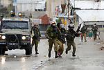 Israeli security forces run during clashes with Palestinian protesters following the funeral of Hamza Zamareh in Halhoul, in the West Bank city of Hebron on February 17, 2018. Hamza stabbed a security guard at the entrance of the Israeli settlement Karmei Tzur north of Hebron and was shot dead, the Israeli army said, in the latest violence in the occupied West Bank. Photo by Wisam Hashlamoun