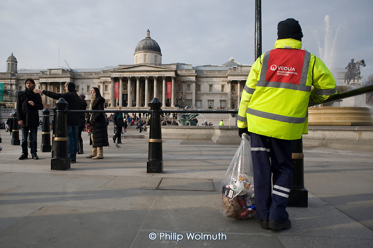 A worker employed by transnational services company Veoila clears litter from Trafalgar Square, London.