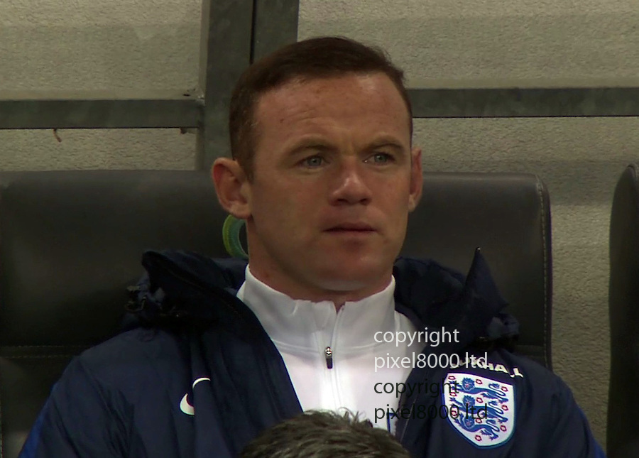 Pic shows:<br /> Slovenia v England<br /> Dropped captain Wayne Rooney  looks rueful  on the bench as the anthems are played.<br /> <br /> <br /> Picture by Pixel8000 07917221968