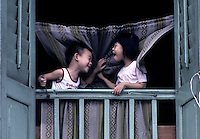 Playtime for these two children at a window of old China Town in Singapore
